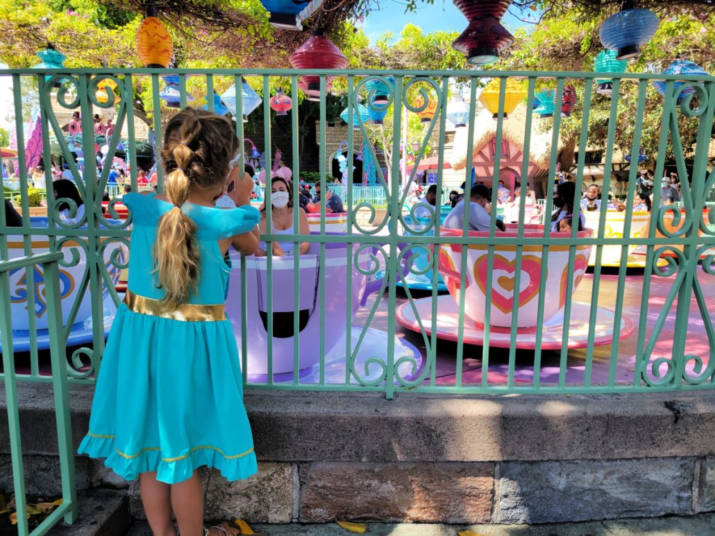 Girl watching the Mad Tea Party teacups ride at Disneyland through the bars