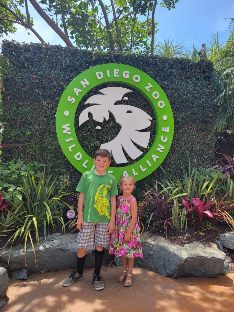 kids standing in front of entrance sign at the san diego zoo