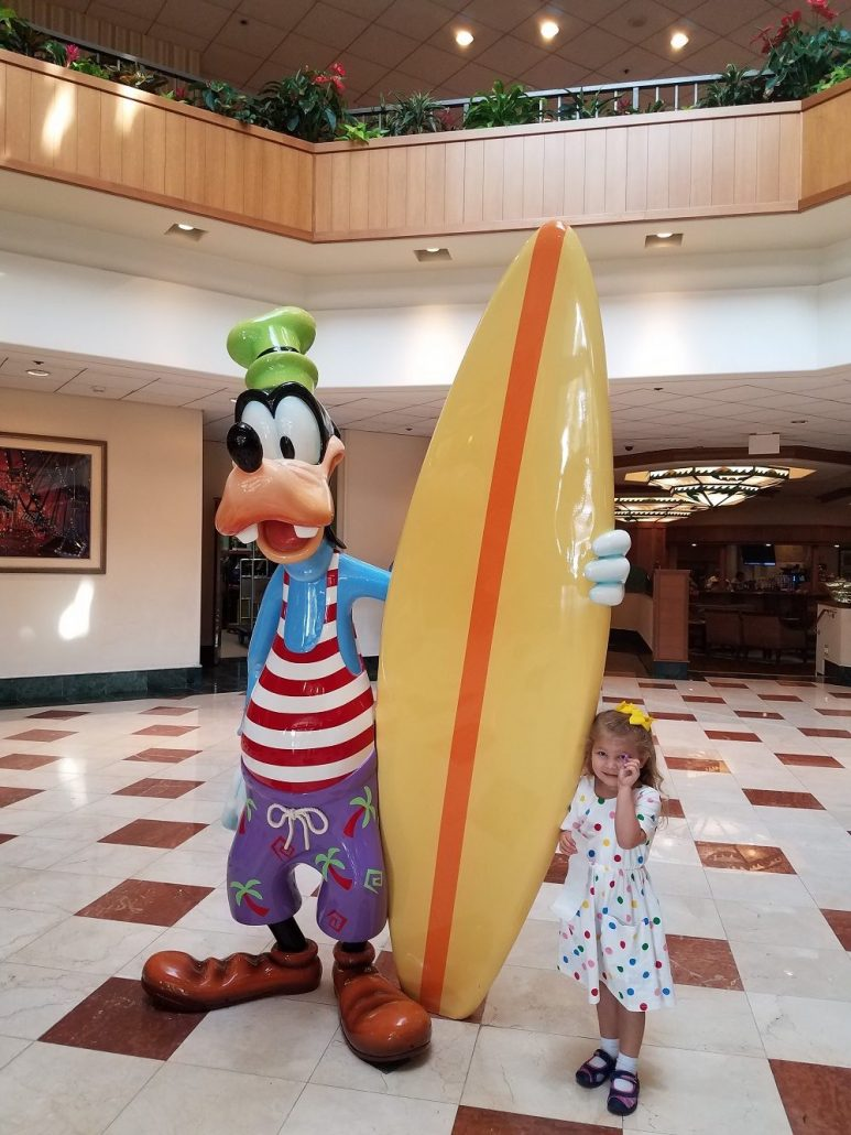 Little girl poses with Goofy statue inside Paradise Pier hotel at Disneyland resort