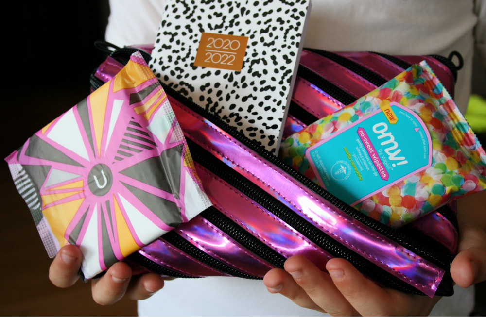 Tween holding a pink bag with period supplies including cleansing wipes and pad
