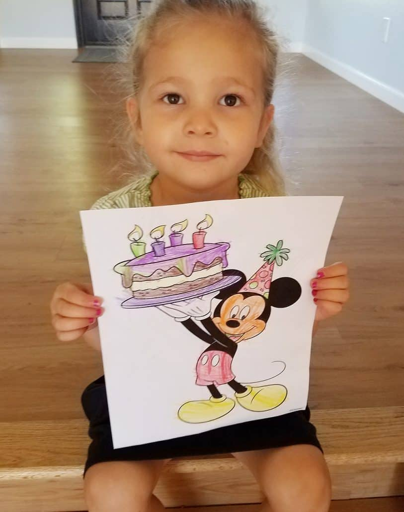 Preschool girl holding a colored drawing of Mickey Mouse holding a birthday cake