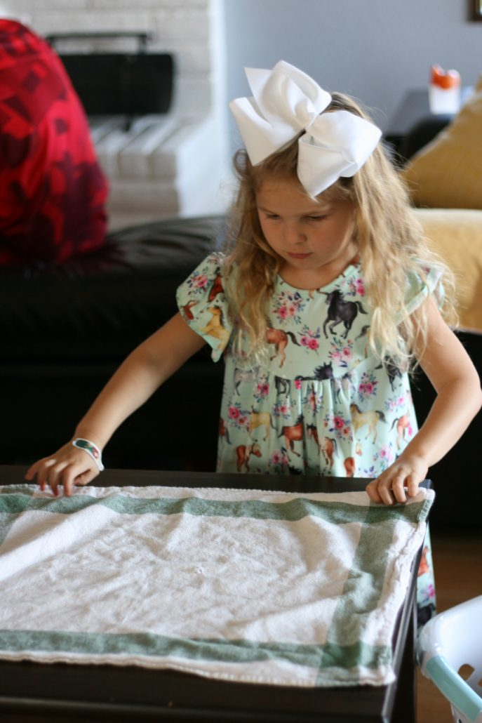 Preschool girl folding a dish towel