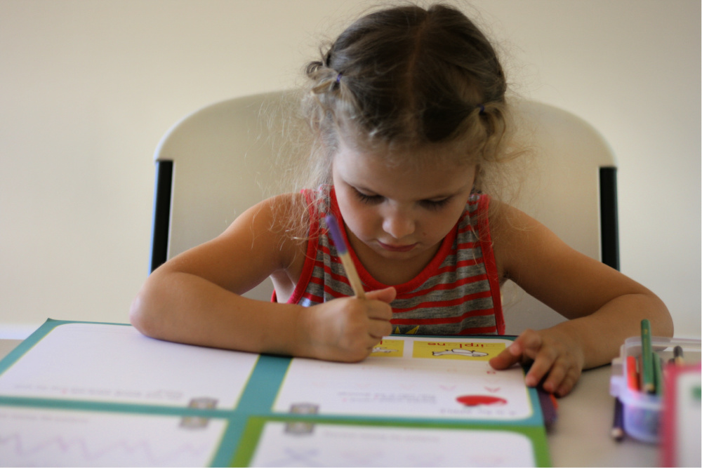 Preschool girl doing a workbook with colored pencil and paper