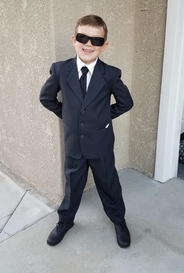 Little boy dressed in a suit as one of the Men in Black for Halloween