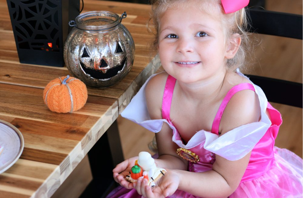 Little girl in princess dress holding a Halloween treat