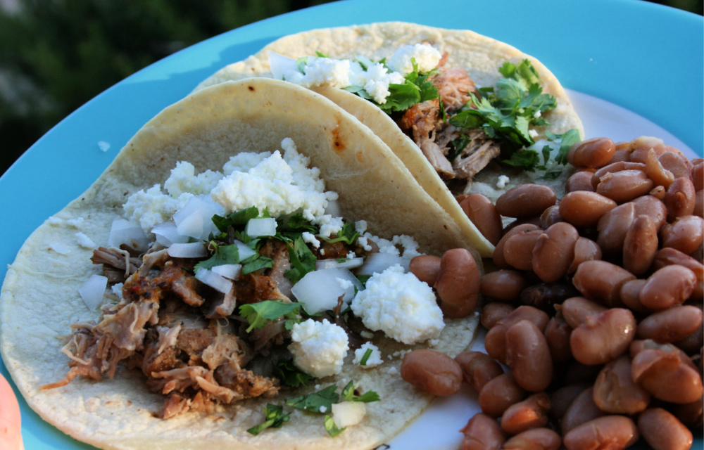 Pork carnitas tacos with side of pinto beans