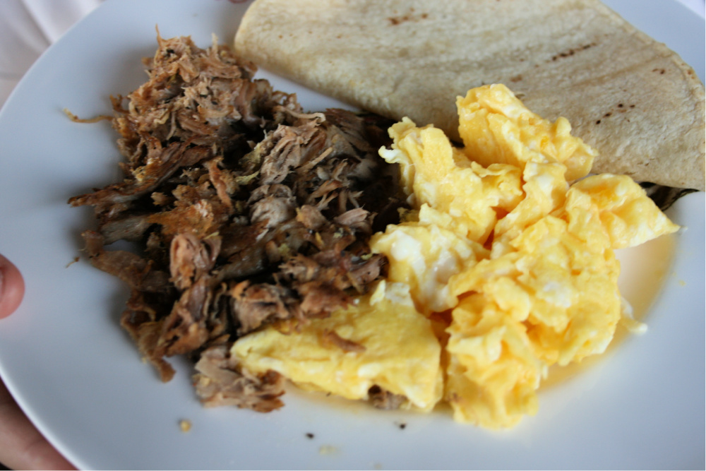 Pork carnitas with scrambled eggs and corn tortilla