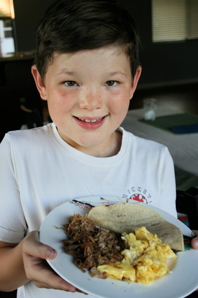 Young boy holding a plate of food with Mexican pork carnitas, corn tortilla and scrambled eggs