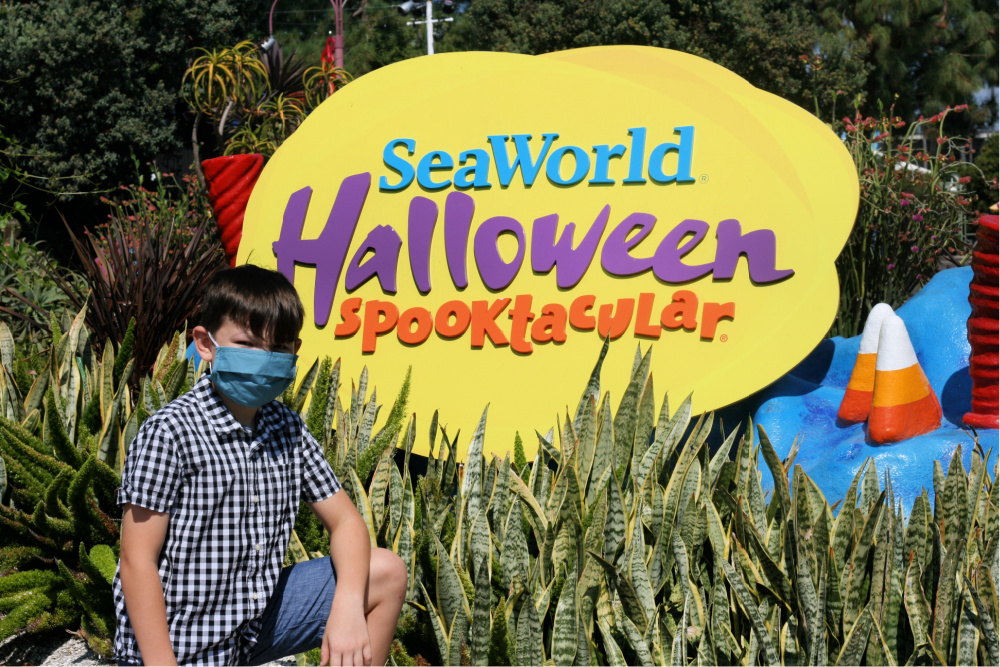 Boy wearing a face mask posing next to SeaWorld Halloween Spooktacular sign