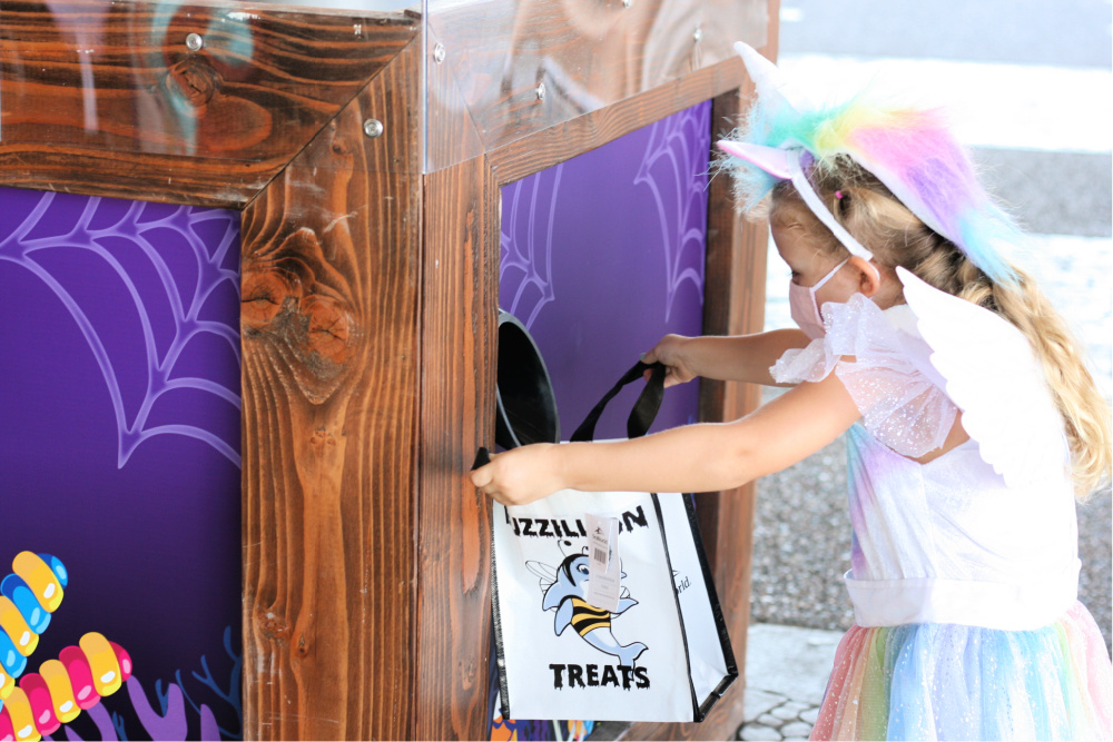 Little girl holding treat bag at candy chute during SeaWorld Halloween spooktacular