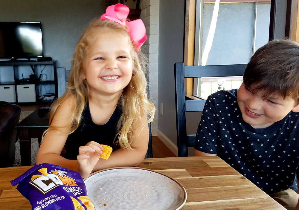 Little girl laughs while eating a chip as older brother looks on