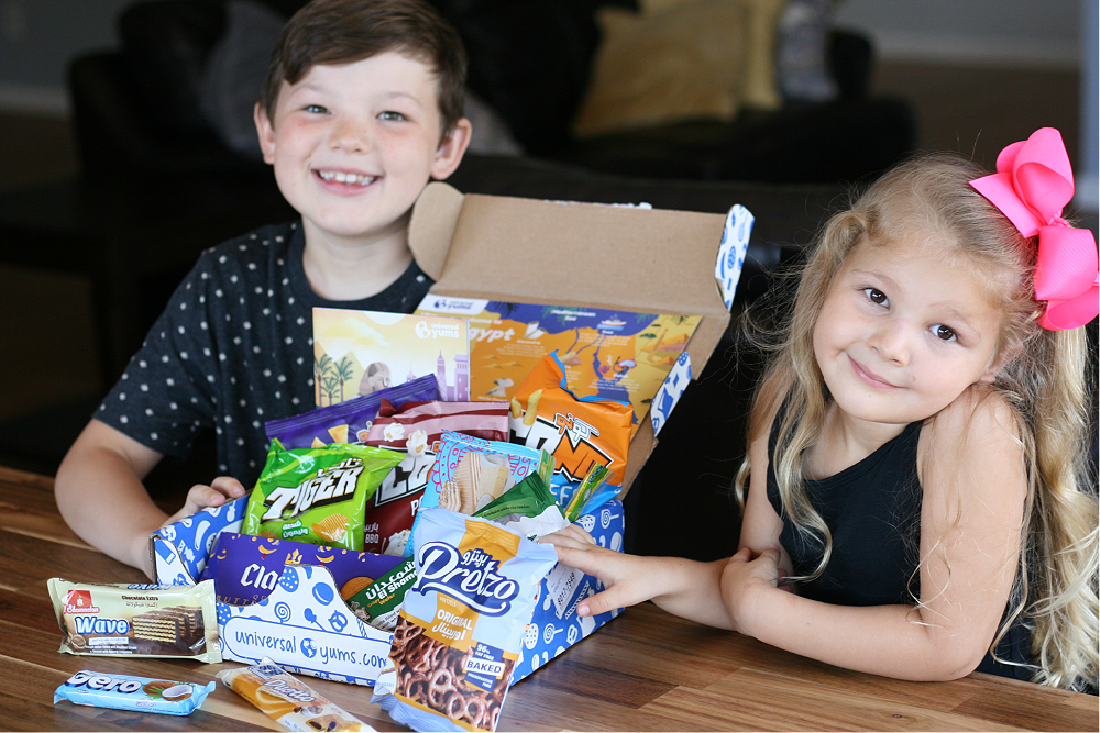 Boy and girl smiling next to the Universal Yums box from Egypt