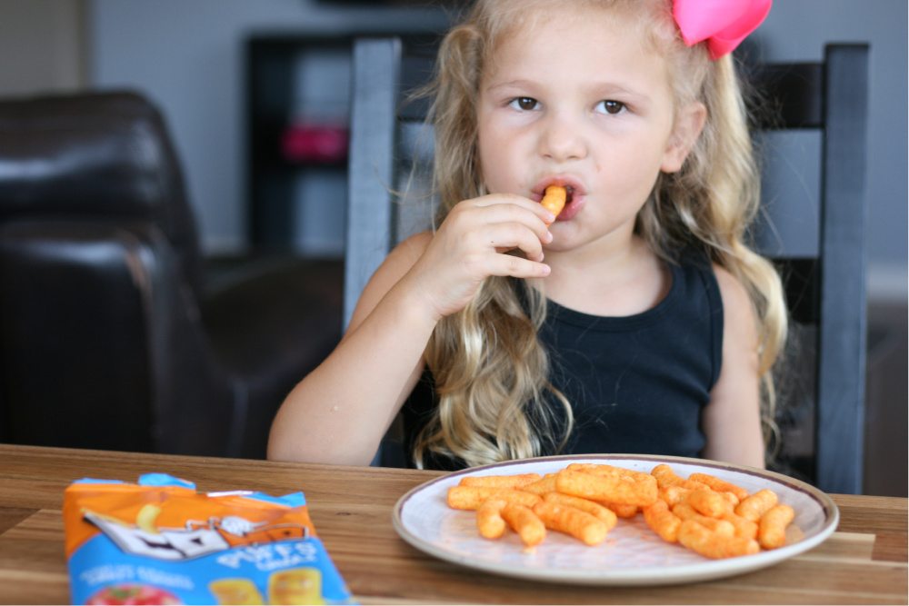 Little girl eating tomato puff chips