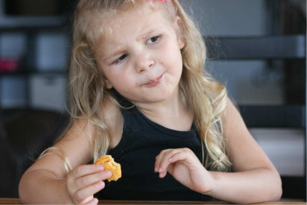 Little girl making curious face as she eats a potato chip