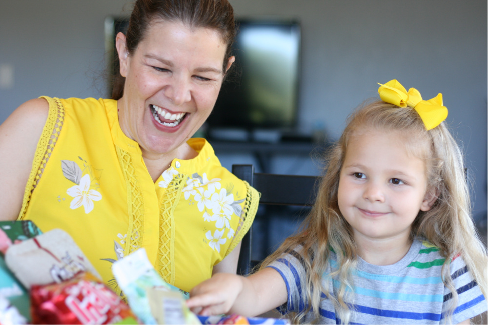 Mom and preschool daughter laughing as they point to snacks in a box