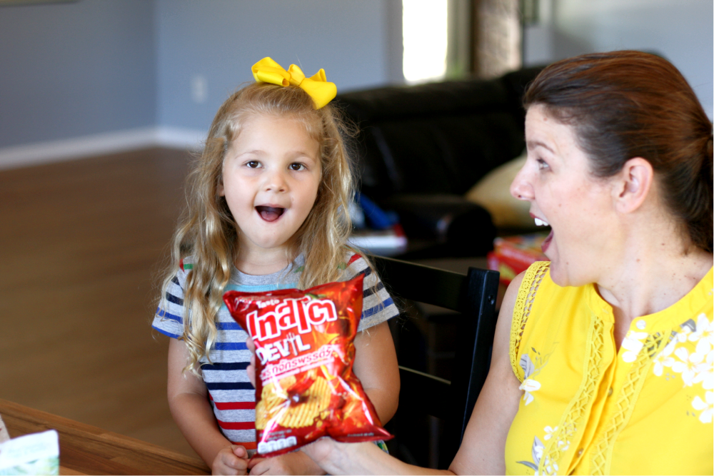 Little girl making surprised face ready to taste spicy chips from Universal Yums box