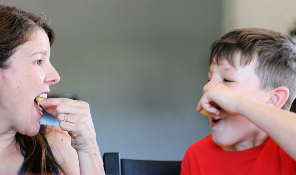 Mom and son enjoying Universal Yums snacks, taking a bite of chips at same time