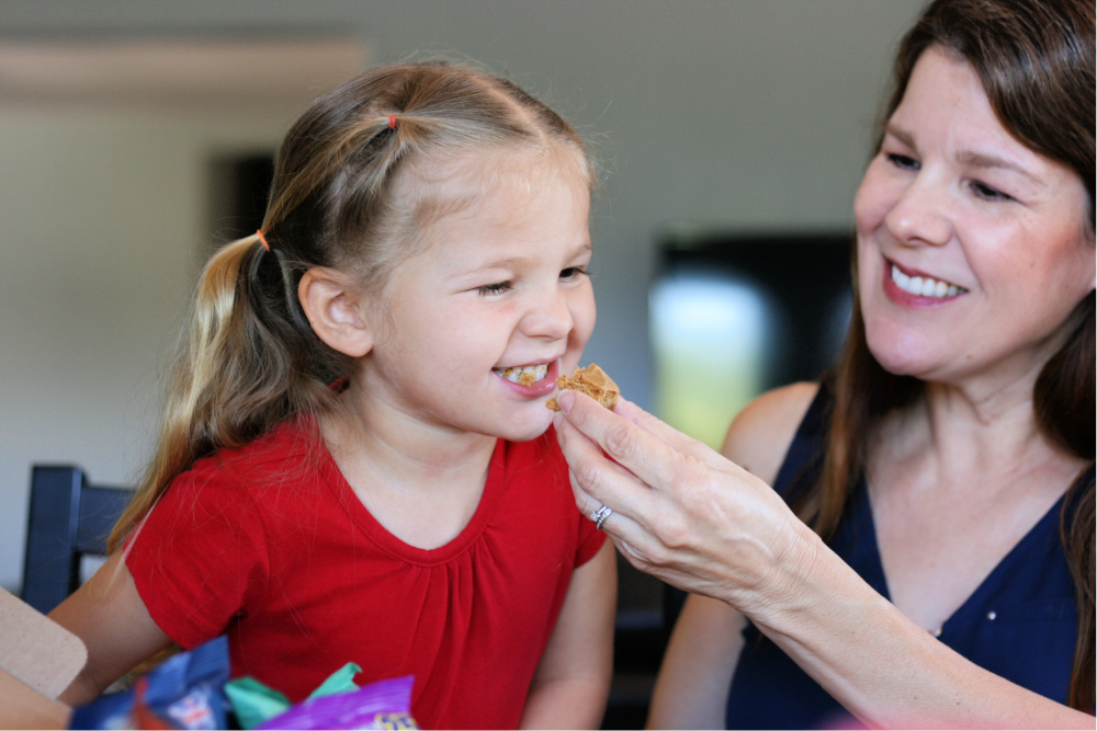 Mom feeding preschooler a snack from the Universal Yums box