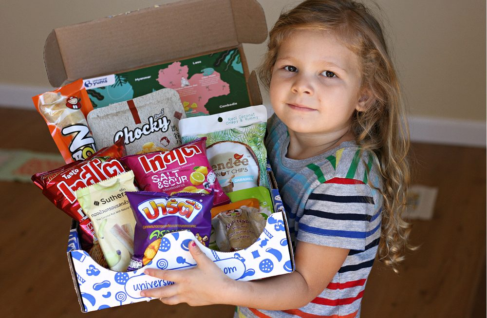 Little girl in striped dress holding Universal Yums box from Thailand