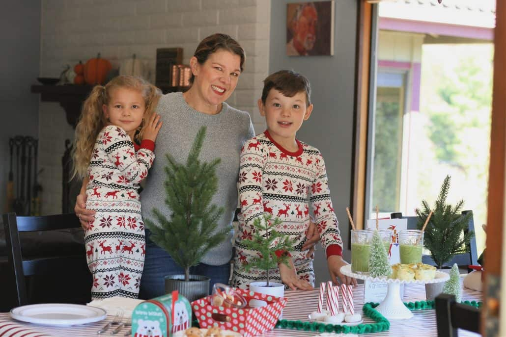 Mom and two kids, wearing Christmas pajamas standing at breakfast table for Christmas