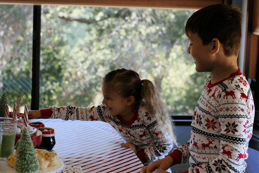 Boy and girl wearing Christmas pajamas standing at breakfast table