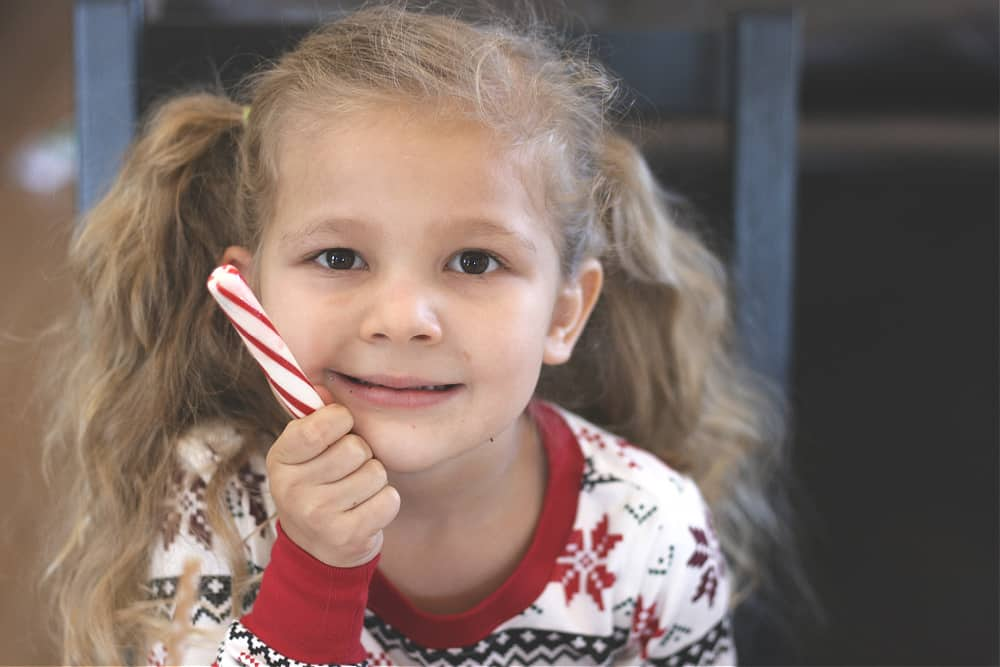 Little girl wearing Christmas pajamas and holding a peppermint stick