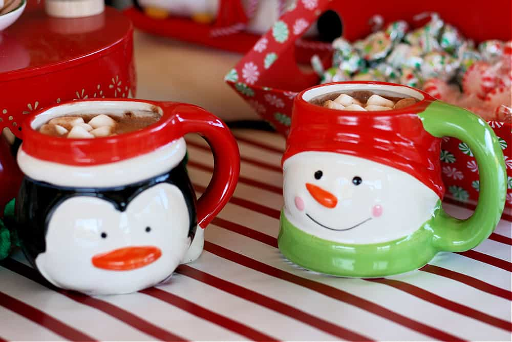 Penguin and Snowman Christmas mugs filled with cocoa and marshmallows