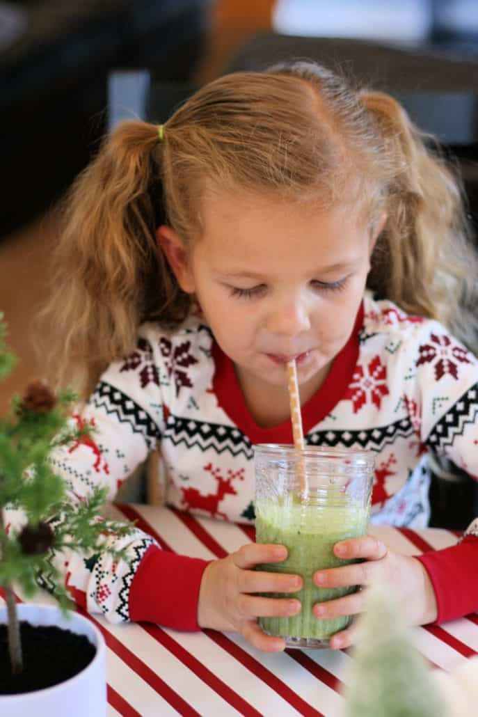 Little girl sips green smoothie through a straw
