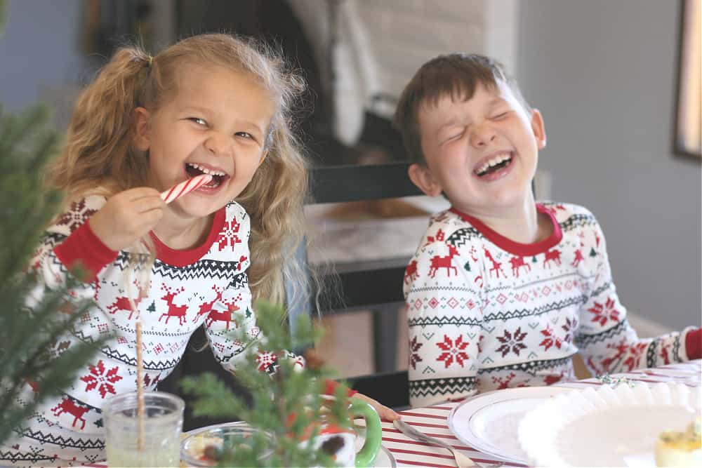 Little boy and girl wearing Christmas pajamas and laughing