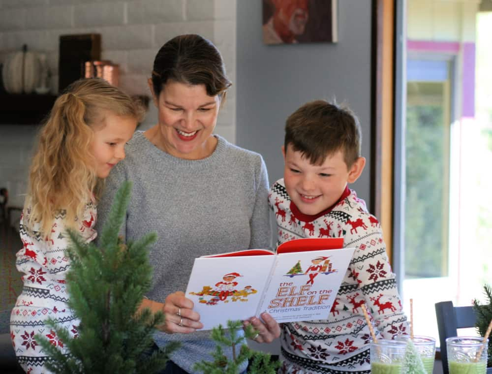 Mom reading Elf on the Shelf book to two young kids