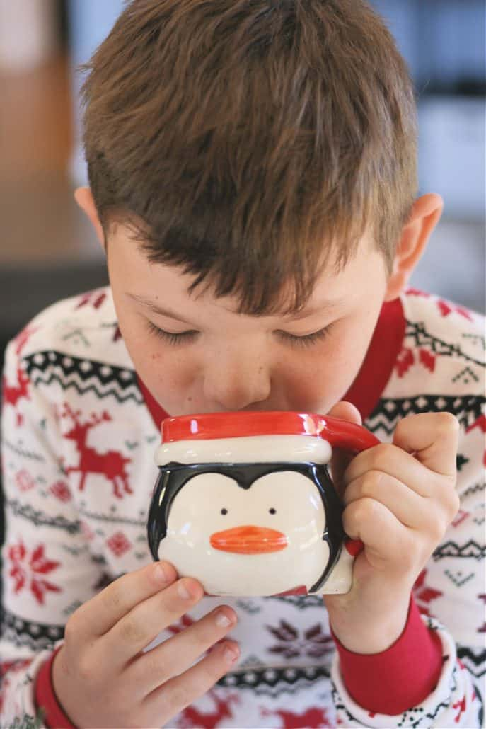 Little boy wearing Christmas pajamas sipping hot cocoa from a penguin mug
