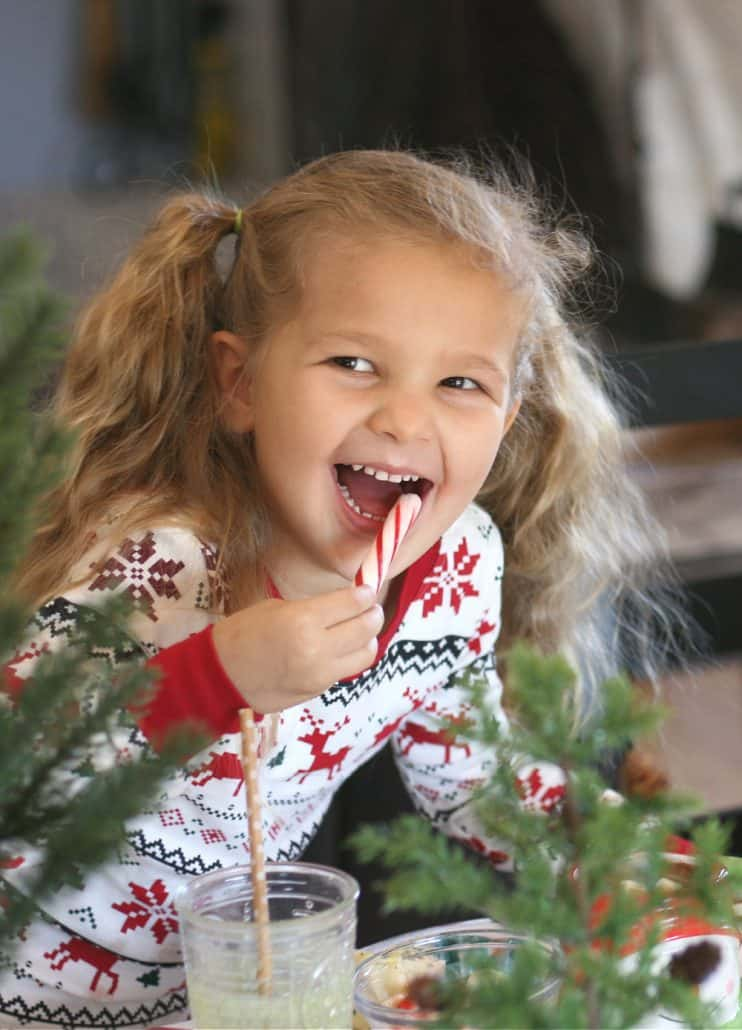 Little girl wearing pajamas eating a peppermint stick