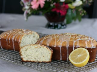 Loaf of Poppy Seed bread with lemon glaze next to a slice and half a lemon