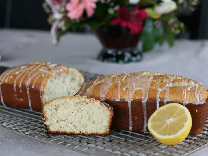 Loaf of Poppy Seed bread with lemon glaze next to a slice and half a lemon