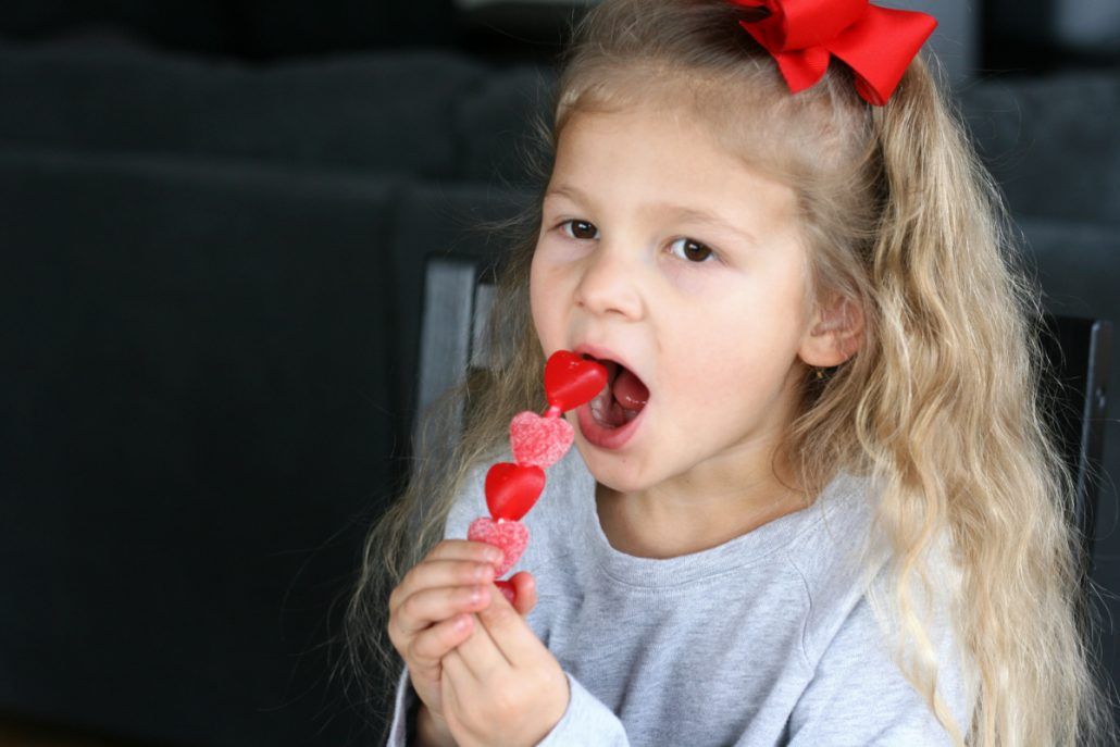 Little girl eating gummy heart candies on a stick