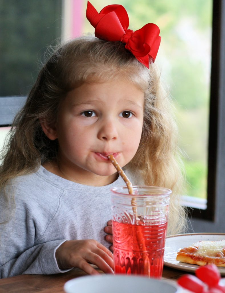Little girl sipping pink punch from a straw