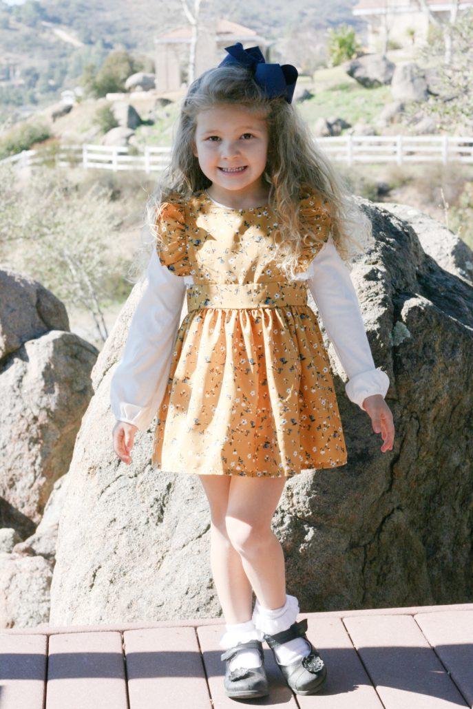 Little girl wearing retro mustard yellow floral dress