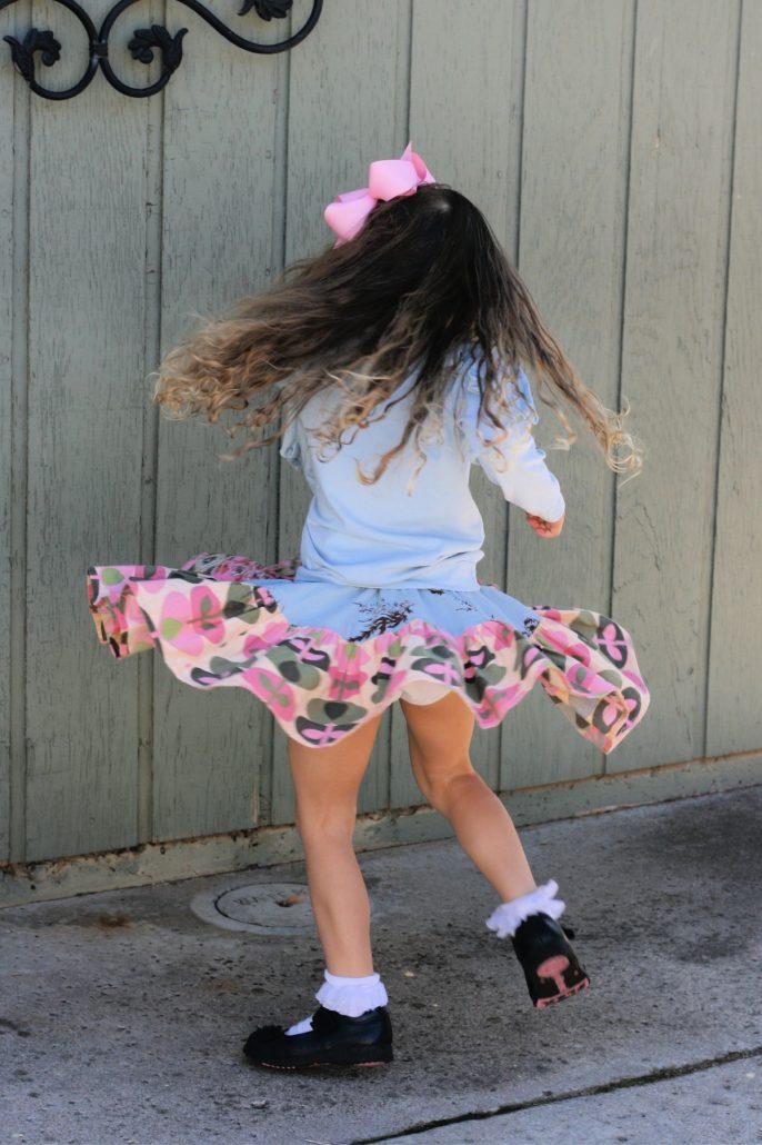Little girl twirling in Matilda Jane skirt