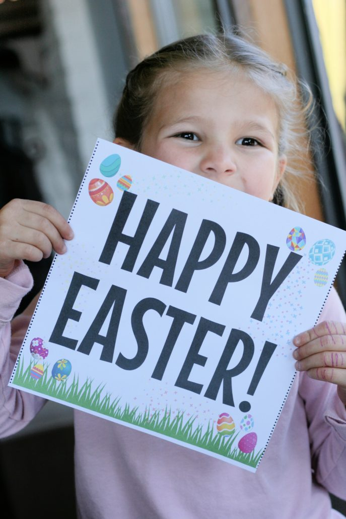 "Little girl holding a ""Happy Easter"" sign"