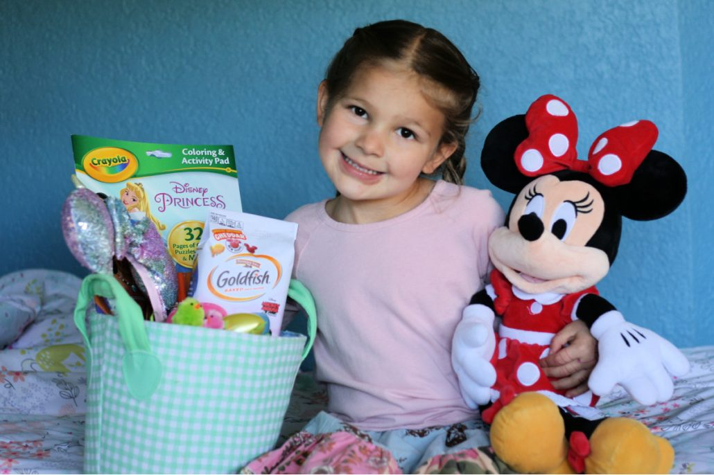 Little girl sitting with Easter basket and Minnie Mouse plush toy