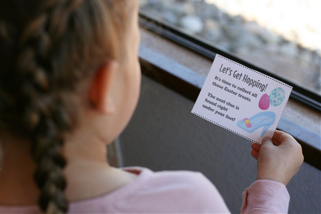 Back of little girl's head holding a paper clue in Easter scavenger hunt