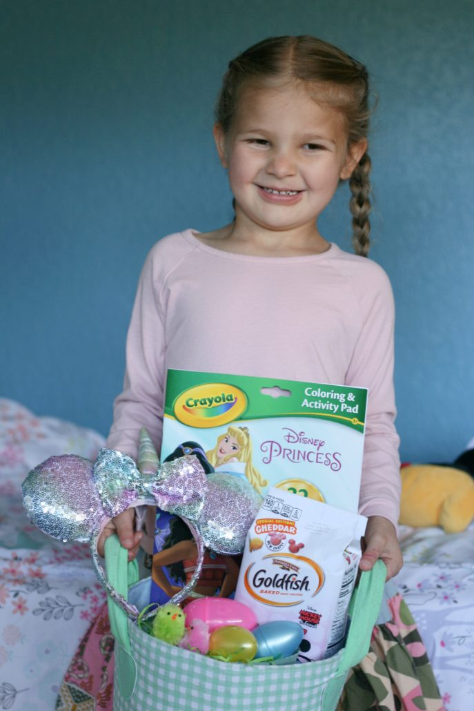 Little girl on a bed holding an Easter basket filled with gifts