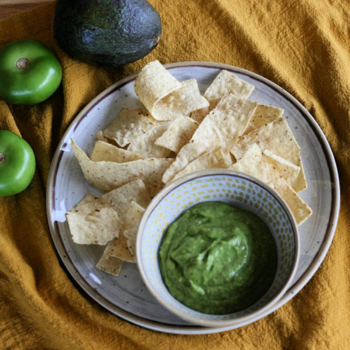 Overhead shot of tomatillo salsa in a bowl with chips