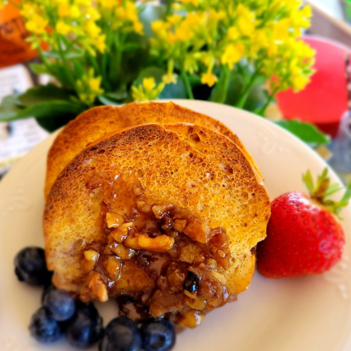 Overnight French toast with berries on a plate in front of yellow flowers
