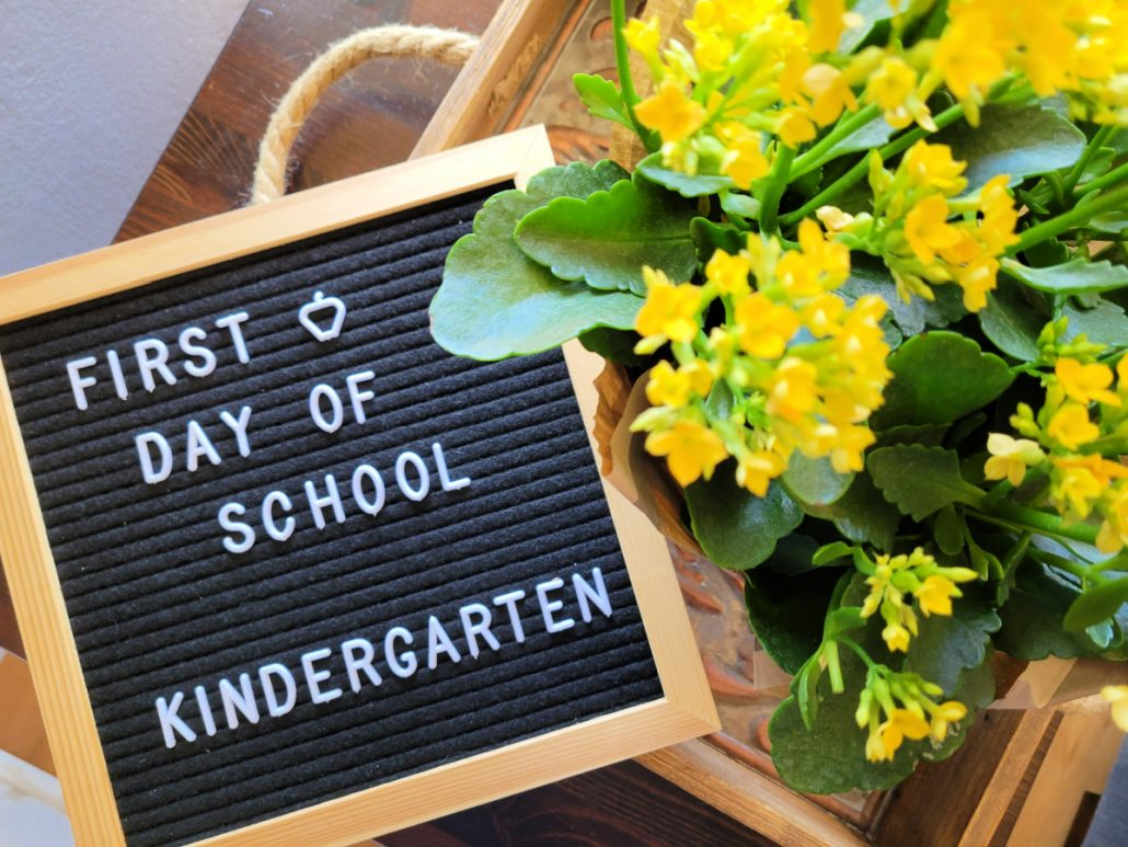 Sign that says First Day of School - Kindergarten next to yellow flowers