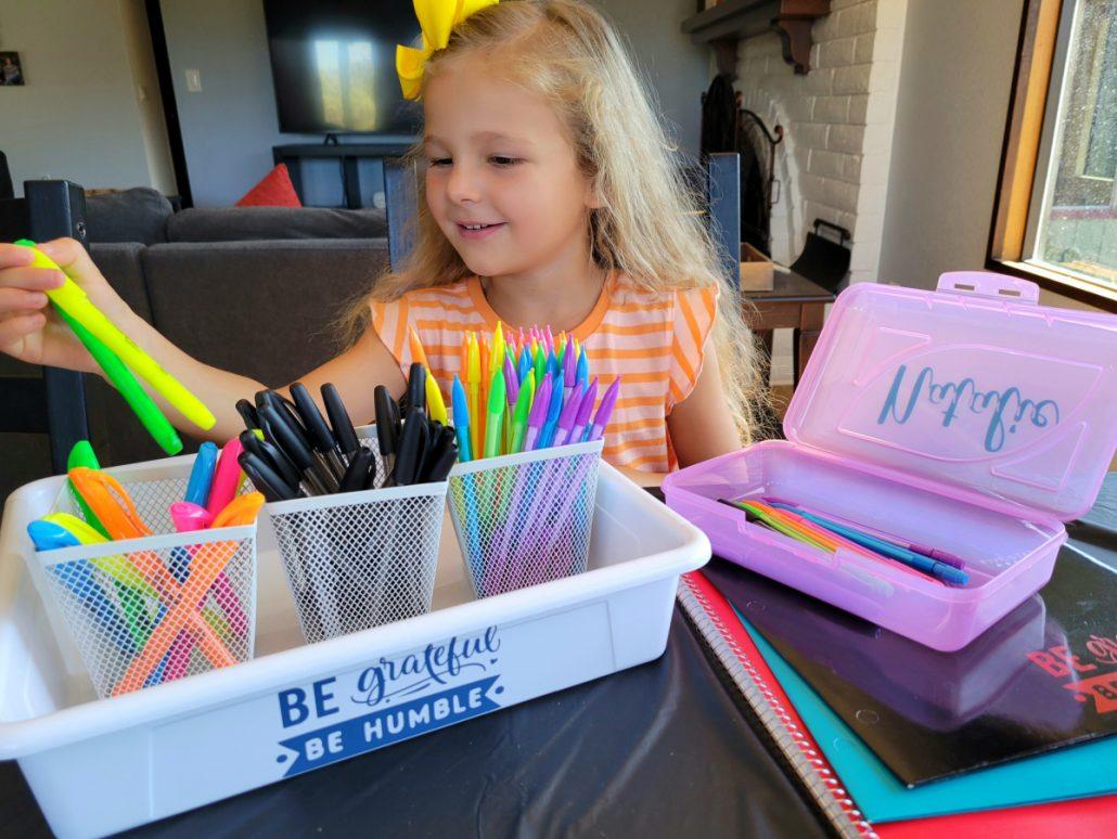 Little girl choosing school supplies from a bin