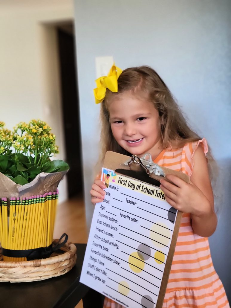 Young girl holding a back to school interview page on a clipboard